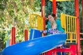 Girl with mom on children's slide — Stockfoto