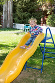 Girl on children's slide on playground — Stock Photo