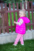 Child girl in park near fence — Stock Photo