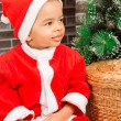 African American boy dressed costume Santa Claus by fireplace. Christmas and New Year — Stock Photo #62259867