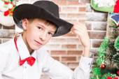 Boy gentleman in a hat by fireplace. Christmas and New Year — Stock Photo