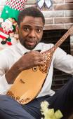 African American man with Musical instrument Dombra by fireplace. Christmas and New Year — Stock Photo