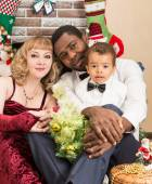 Happy family: black father, mom and baby boy by fireplace. Christmas and New Year — Stock Photo