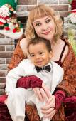 Happy mother and black baby boy cuddling by fireplace. Christmas and New Year — Stock Photo