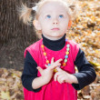 Cute child girl playing with fallen leaves in autumn park — Stock Photo #62260497