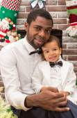 Happy black father and baby boy cuddling by fireplace. Christmas and New Year — Stock Photo