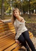 Young girl sitting on a yellow bench — Stock Photo