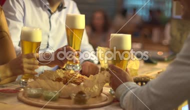 Friends clink glasses of beer at a bar — Stock Video