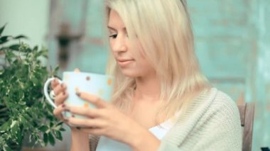 Beautiful, blonde young woman drinking tea in the garden — Stock Video