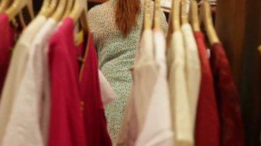 Женщина выбирает одежду в магазине — Стоковое видео