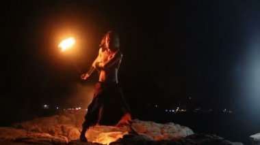 Male Artist of the spins fire poi on a rock — Stock Video