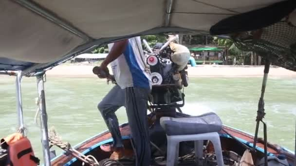 Man steers the boat in the tropics