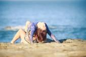 Gymnast girl on a rock against sea — Stock Photo