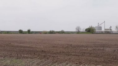 Car driving on a road plowed field of granaries — Stock Video