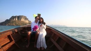 Bride and groom in thai boat — Stock video