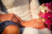 Bride and groom hands  with bouquet — Stock Photo