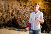 Groom against tree roots at beach — Stock Photo