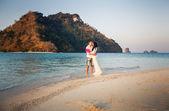 Bride and groom on sea beach — Stock Photo