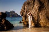Bride at rock on sea beach — Стоковое фото