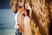 Bride and groom on rocky beach — Стоковое фото