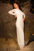 Bride at rock on beach — Стоковое фото