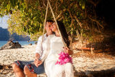 Bride with groom on rope swing — Stock Photo