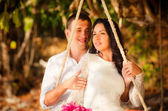 Bride and groom on rope swing — Stockfoto