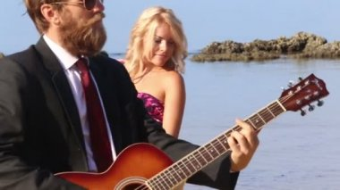 Girl and man with guitar on beach — Stock Video