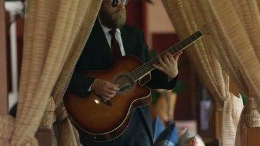 Uomo barbuto in abito nero suona la chitarra — Video Stock