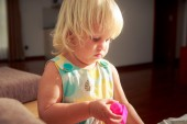 Blonde girl plays toy constructor — Stock Photo