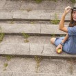 Young girl wearing a hat sitting on stone steps — Stock Photo #51830829