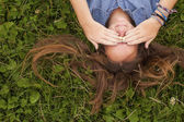 Girl lying on the grass covering eyes with hands. — Stock Photo