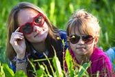 Sisters lying in the grass — Stock Photo