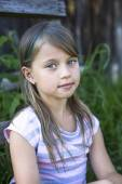 Cute little girl near a country house. — Stock Photo