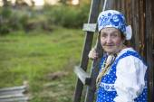 Old woman in russian ethnic clothes — Stock Photo
