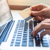 Hands with credit card and laptop — Stock Photo
