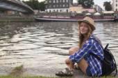 Girl sitting on stone embankment — Stock Photo