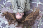 Girl in a sweater lying on stone — Stock Photo