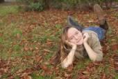 Girl lying on fallen leaves — Stock Photo