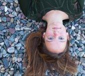 Girl lying on river pebbles — Stock Photo