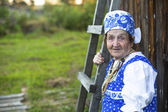 Old woman in village — Stock Photo