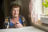 Old woman alone near a window — Stock Photo