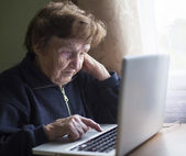 Old woman works on laptop — Stock Photo