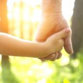 Adult holding child's hand — Stock Photo