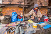 Unidentified shoemaker works on the street. — Stock Photo