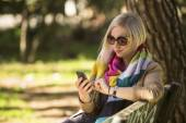 Young woman with smartphone in hands — Stock Photo