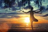 Silhouette of girl meditating on the sea beach — Stock Photo