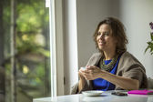 Woman sits in front of the window — Stock Photo