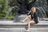 Young attractive blonde woman on fountain — Stock Photo