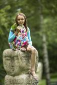 Little girl sitting on stone totem — Stock Photo